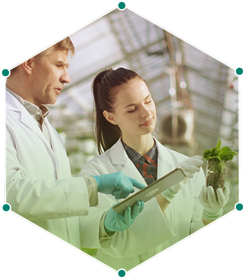 a male and female wearing lab coats examining a plant
