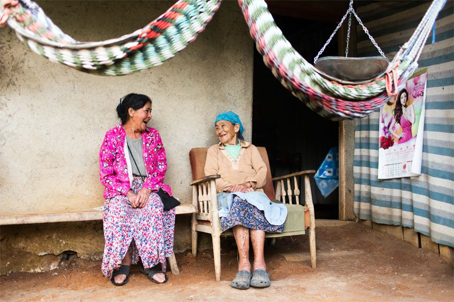 Arcadia and her 90-year-old mother, Victorina, talk and laugh on the porch of their home.