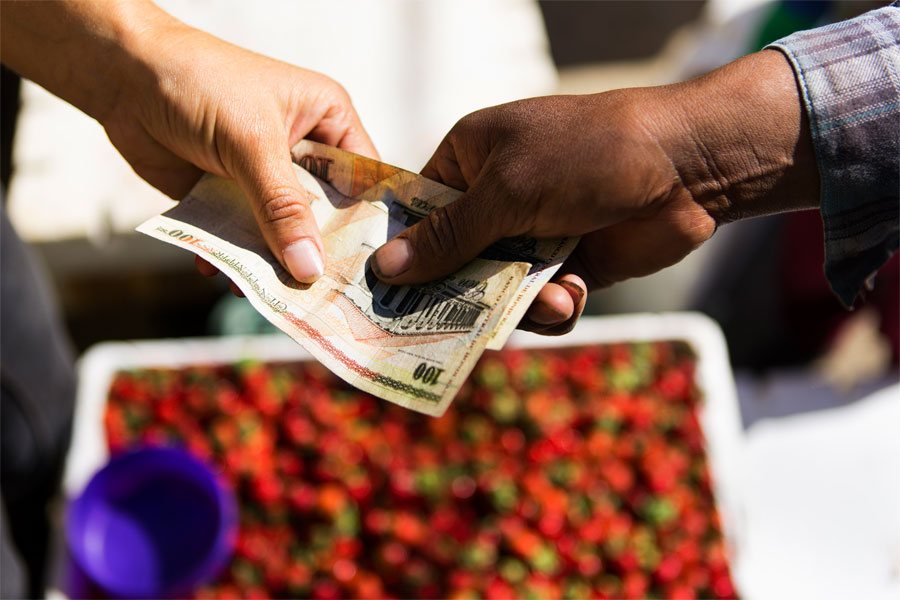 Emiliano being paid by a customer after delivering strawberries at the local market in la Esperanza.