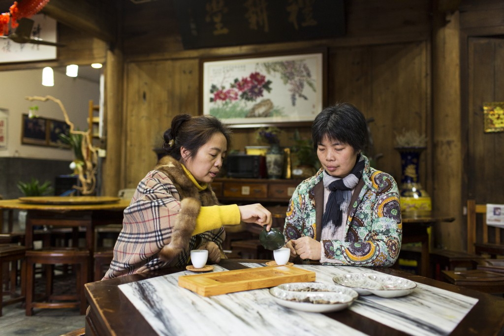 Weng yun Juan (left) and Weng Yung Hua (right) drinking tea at the Li Geng Tang Tea House in Meijiawu Tea Village, China.