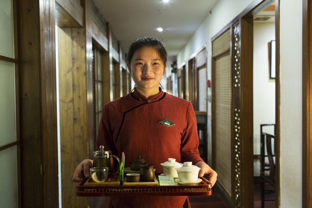Waitress Xiao Juan Zhu with a tray of tea at the Qing Teng Tea House in Hangzhou City, China.