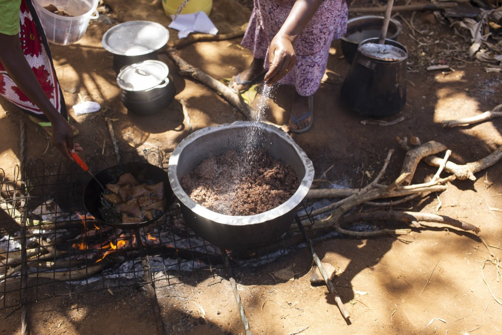 Cecilia Mwikali Kyalo cooking sorghum at home, Kiatine Village, Kenya