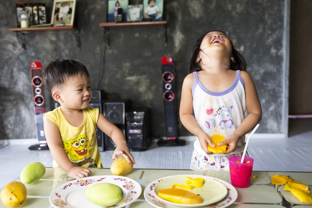 Lorraine, aged 2 and Liam, aged 1, eating mangos, Alix, Batangas City, Philippines.