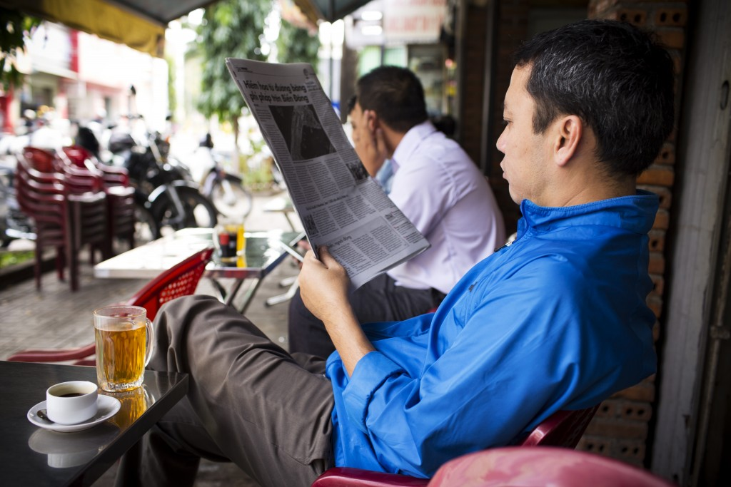 A local man reads the paper while enjoying coffee and tea at a coffee house in Buon Ma Thuot, Vietnam