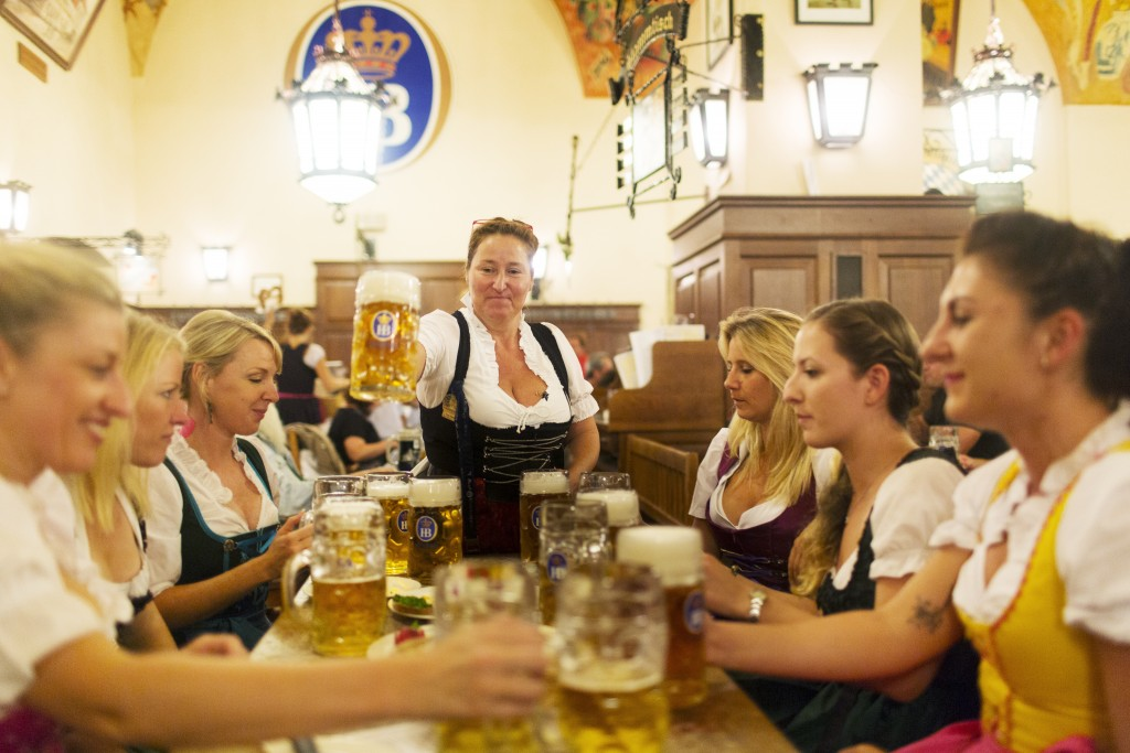 A waitress serves beers to a group of friends on a pre-wedding 'Hen Party' at the Hofbrauhaus, Munchen, Germany